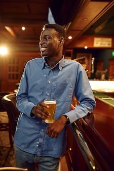 Młody człowiek pije świeże piwo przy ladzie w barze. ludzie relaksują się w pubie, nocny tryb życia, mężczyzna przy szklance trunku