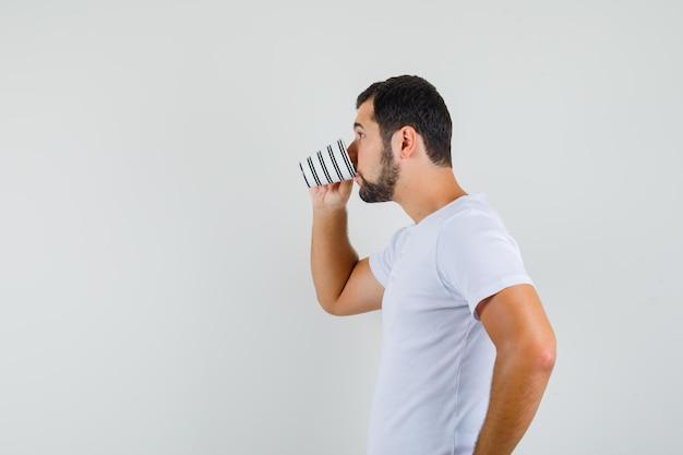 Młody człowiek pije w białej koszulce i wygląda spokojnie. miejsce na tekst