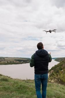 Młody człowiek pilotuje drona w przyrodzie
