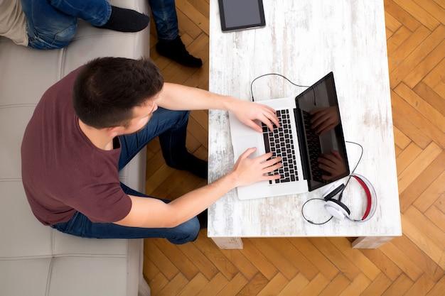 Młody człowiek pisania na swoim laptopie