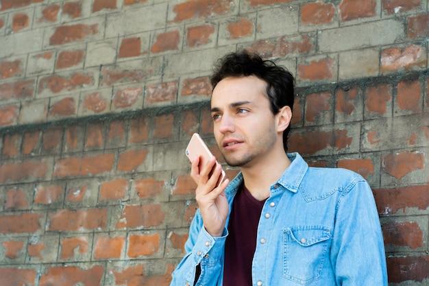 Młody człowiek pisania na swoim telefonie.