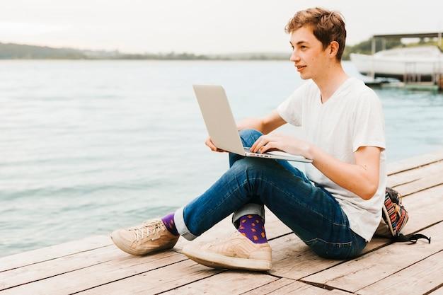 Młody człowiek pisze na laptopie nad jeziorem