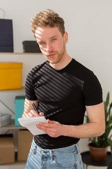 Młody człowiek pisze na notatniku