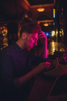 Młody człowiek pisze na starej maszynie do pisania. w ciemnym świetle, restauracja, nowoczesne ubrania, stare nawyki pisarza