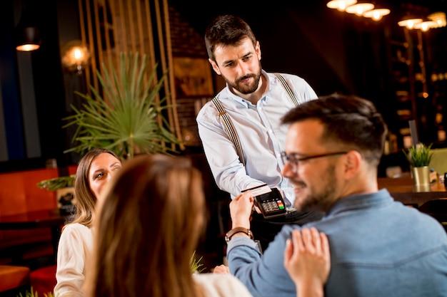 Młody człowiek płaci kartą kredytową zbliżeniową w restauracji