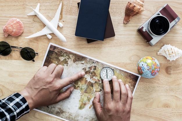 Młody człowiek planowania podróży na wakacje wycieczka z mapą. widok z góry.