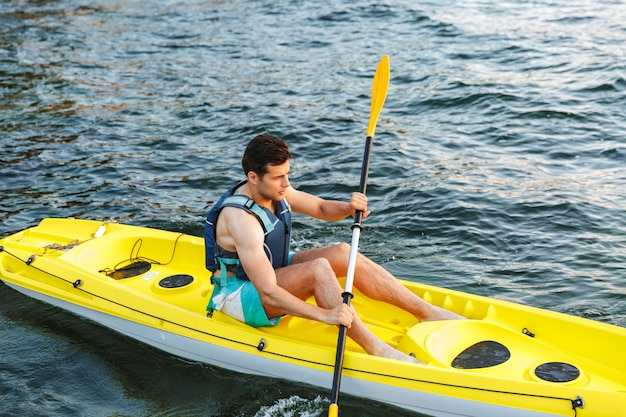Młody człowiek, pływanie kajakiem po jeziorze