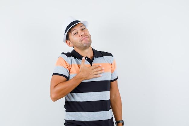 Młody człowiek pochyla głowę ręką na klatce piersiowej w koszulce i kapeluszu i wygląda uroczo