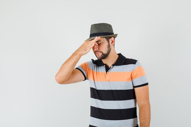 Młody człowiek pocieranie oczu i nosa w t-shirt, kapelusz i wyglądający na zmęczonego
