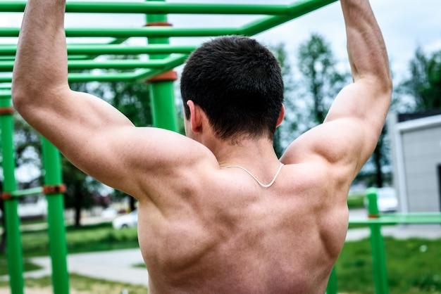 Młody człowiek podciąga się na poziomym pasku na zewnątrz na boisku sportowym. street workout.