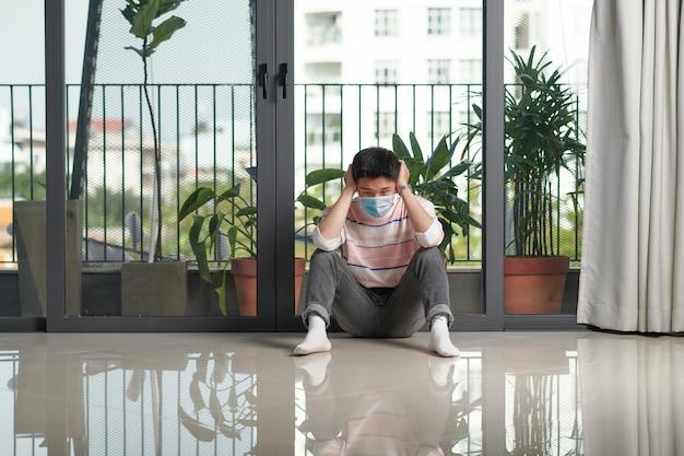 Młody człowiek podczas pandemii koronawirusa nosi maskę na twarz w domu w celu zachowania dystansu społecznego