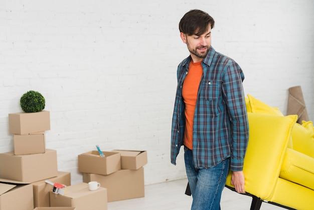 Młody człowiek podnosi żółtą kanapę w jego nowym domu
