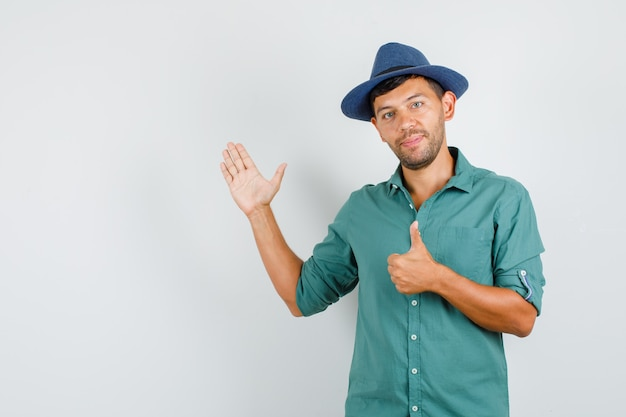 Młody człowiek podnosząc otwartą dłoń z kciukiem do koszuli