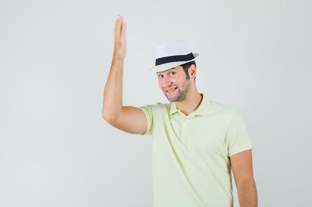 Młody człowiek podnosząc ramię w t-shirt, kapelusz i wesoły wyglądający.