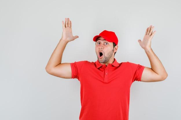Młody człowiek, podnosząc ramiona w czerwonej koszulce