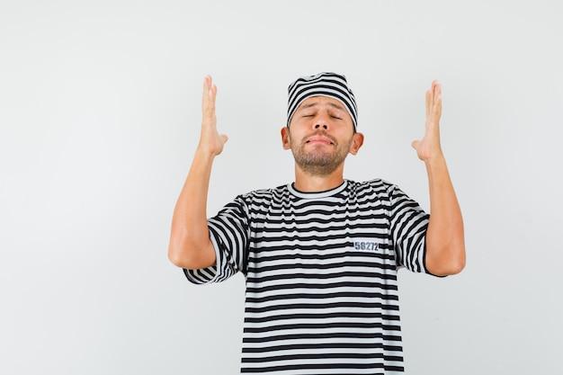 Młody człowiek, podnosząc ręce i ręce w pasiastej koszulce, kapeluszu i patrząc z nadzieją.