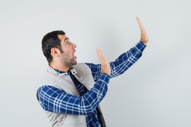 Młody człowiek podnosząc ręce z otwartą dłonią na bok, aby bronić koszuli, kurtki bez rękawów i wyglądającego na przestraszonego. przedni widok.