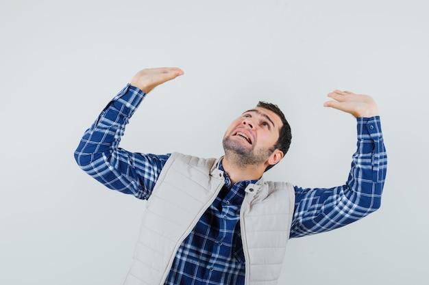 Młody człowiek, podnosząc ręce z otwartą dłonią w koszuli, kurtce bez rękawów i patrząc przestraszony, widok z przodu.