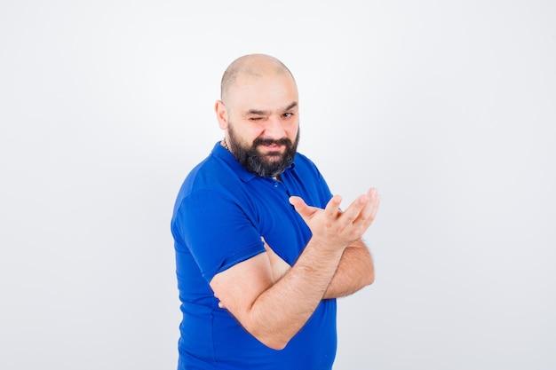 Młody człowiek podnosząc rękę z otwartą dłonią na bok, mrugając w niebieskiej koszuli, widok z przodu.
