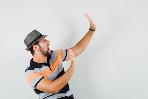 Młody człowiek podnoszący dłonie w geście ochronnym w koszulce, kapeluszu i patrząc przestraszony.