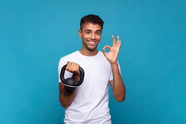 Młody człowiek podnoszący hantle czując się szczęśliwy, zrelaksowany i usatysfakcjonowany, okazując aprobatę gestem ok, uśmiechając się