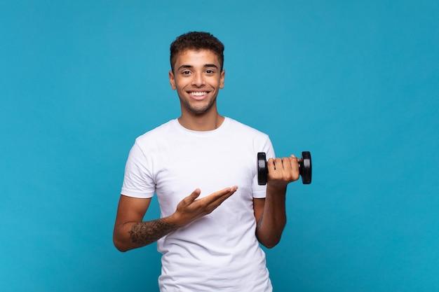 Młody człowiek podnoszący hantle, uśmiechając się radośnie, czując się szczęśliwy i pokazując koncepcję w przestrzeni kopii z dłonią