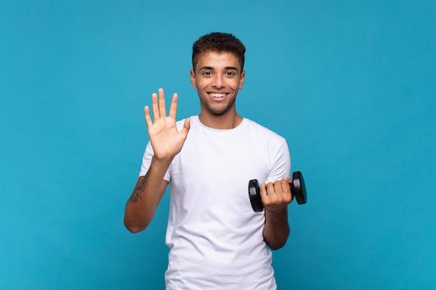 Młody człowiek podnoszący hantle, uśmiechnięty i wyglądający przyjaźnie, pokazujący numer pięć lub piąty z ręką do przodu, odliczający