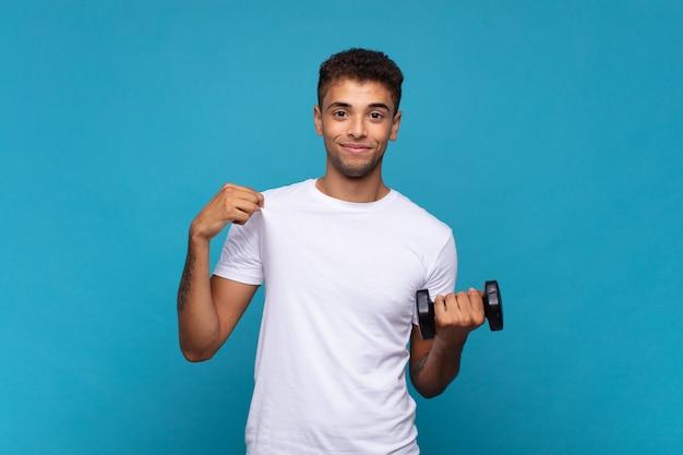 Młody człowiek podnoszący hantle wyglądający arogancko, odnosząc sukcesy, pozytywnie i dumnie, wskazując na siebie