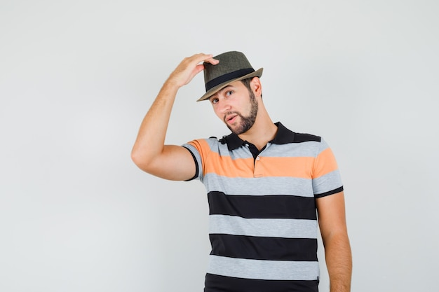 Młody człowiek podnoszący kapelusz w t-shirt i wyglądający elegancko