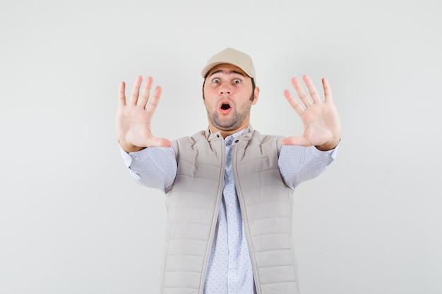 Młody człowiek podnoszący ręce do obrony w koszuli, kurtce bez rękawów, czapce i wyglądający na przestraszonego. przedni widok.