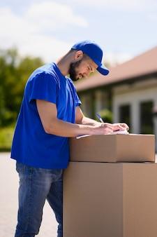 Młody człowiek podpisywania dokumentów dostawy