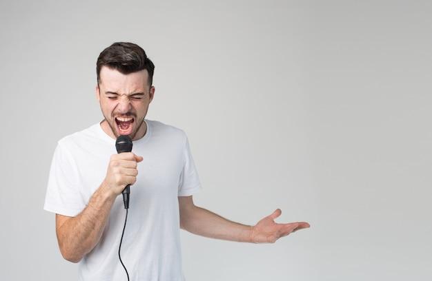 Młody człowiek podpisywania piosenki w mikrofonie