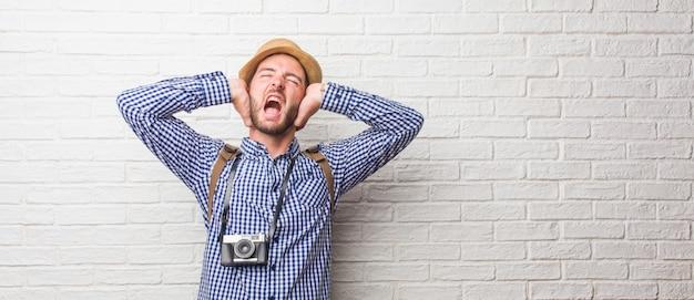 Młody człowiek podróżnik ma na sobie plecak i aparat fotograficzny szalony i zdesperowany, krzyczący poza kontrolą, zabawny wariat wyrażający wolność i dziki