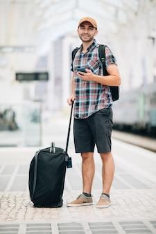 Młody człowiek podróżnik z torbą wygląda w telefonie na stacji kolejowej