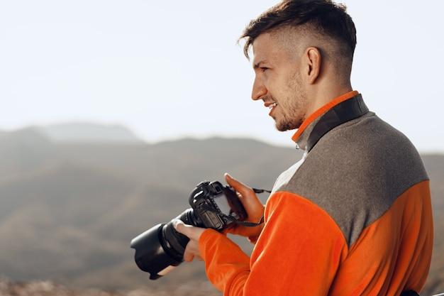 Młody człowiek podróżujący fotografujący góry profesjonalnym aparatem