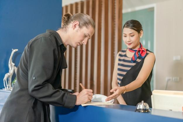 Młody człowiek podróżujący gość wypełniający formularz rejestracyjny podczas zameldowania się z recepcjonistką w hotelu?