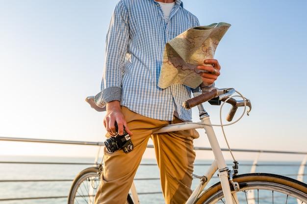 Młody człowiek podróżujący na rowerze drogą morską na wakacje nad morzem o zachodzie słońca, trzymając mapę zwiedzanie z aparatem