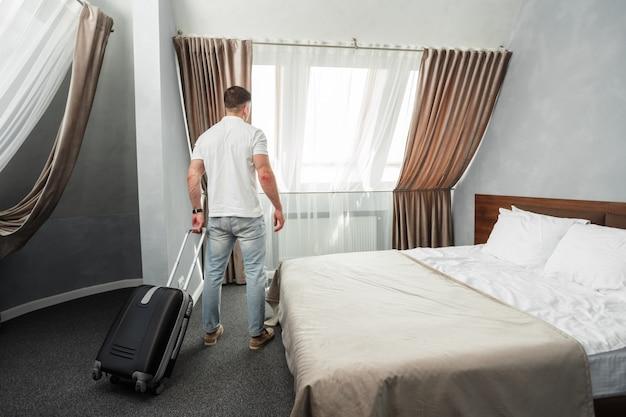 Młody człowiek podróżujący w interesach zakwaterowanie w pokoju hotelowym