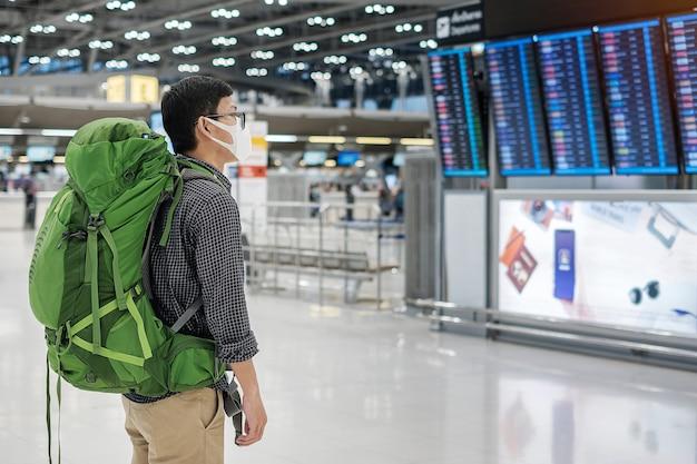 Młody człowiek podróżujący w masce medycznej i sprawdzanie czasu lotu w terminalu lotniska