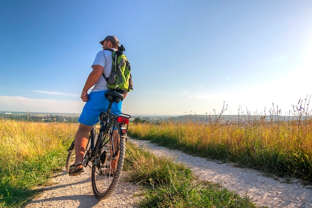 Młody człowiek podróżuje na rowerze w rannym wschodzie słońca z cudownymi promieniami podczas spokojnego lata aktywnego dnia