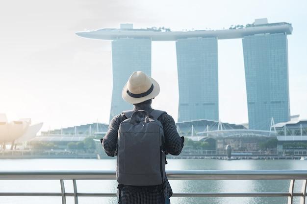 Młody człowiek podróżuje z plecakiem i kapeluszem w ranku, solo azjatycka podróżnik odwiedza w singapur miasta śródmieściu. punkt orientacyjny i popularny wśród atrakcji turystycznych. asia travel concept