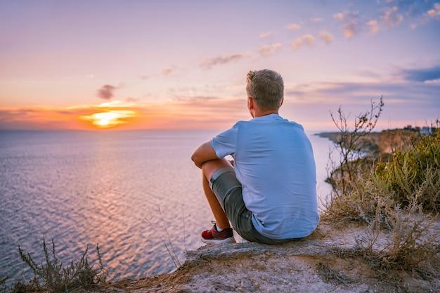 Młody człowiek podziwia niesamowity krajobraz z zachodem słońca na przylądku fiolent na krymie