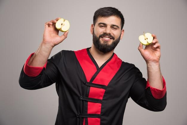 Młody człowiek pokazano plasterki świeżego jabłka.