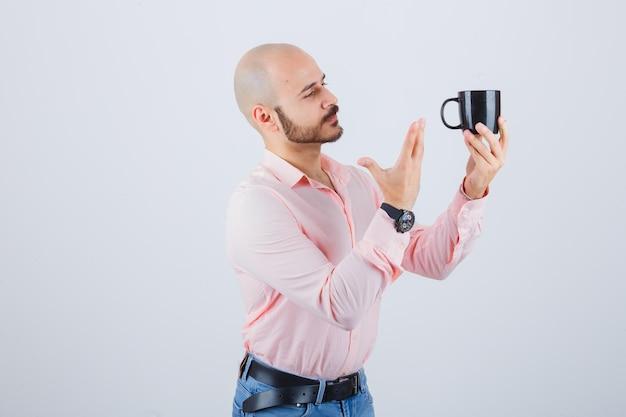 Młody człowiek pokazując czarny kubek w różowej koszuli, dżinsy widok z przodu.