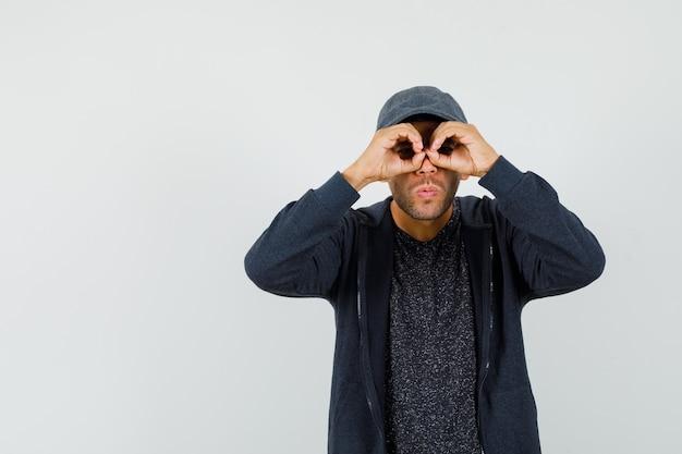 Młody człowiek pokazując gest okularów w t-shirt, kurtkę, czapkę i patrząc zaciekawiony.