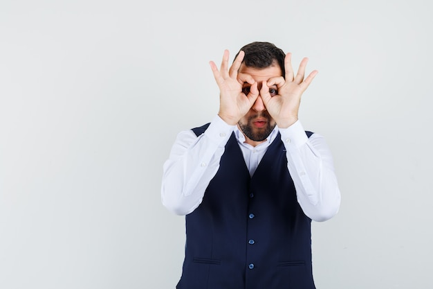 Młody człowiek pokazując gest okulary w koszuli i kamizelce i patrząc skoncentrowany