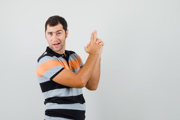 Młody człowiek pokazując gest pistoletu w koszulce i patrząc pewny. przedni widok. miejsce na tekst