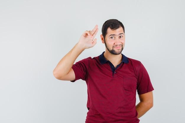 Młody człowiek pokazując gest pożegnania w czerwonej koszulce i patrząc spokojny, przedni widok.