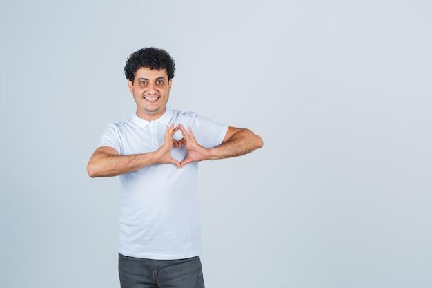 Młody człowiek pokazując gest serca w białej koszulce, spodniach i patrząc wesoło, widok z przodu.
