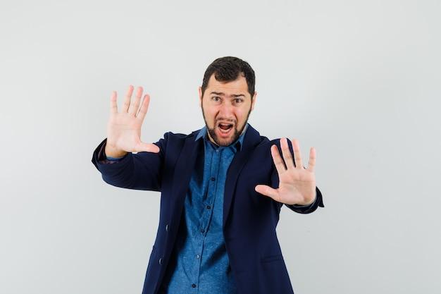 Młody człowiek pokazując gest stop, krzycząc w koszuli, kurtce i wyglądając na przestraszonego